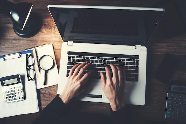 Ręce mężczyzny na klawiaturze laptopa