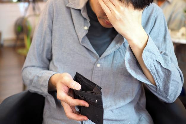 Ręce mężczyzny otwierają pustą torebkę, ubóstwo, zadłużenie i bankructwo w płatności rachunków i kart kredytowych