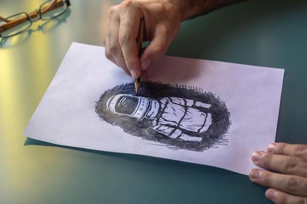 Ręce mężczyzny rysujące ołówkiem astronautę na zielonym szklanym stole z kilkoma szklankami na stole. pojęcie sztuki.