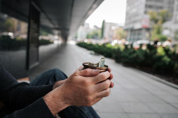 Ręce mężczyzny trzyma kubek z jednego rachunku