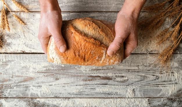 Ręce mężczyzny trzymają bochenek świeżego domowego chleba nad drewnianym stołem z rozsypaną mąką i kłosami pszenicy. widok z góry. naturalne światło.