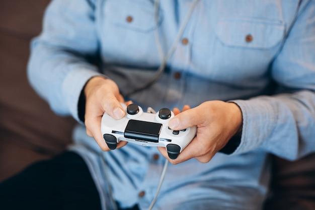 Ręce mężczyzny trzymające kontroler gier. ścieśniać. dobry czas na koncepcję weekendu. wytnij widok męskich rąk. dorosły mężczyzna grając w gry wideo w domu. zwykłe ubrania. spędzanie czasu podczas kwarantanny.