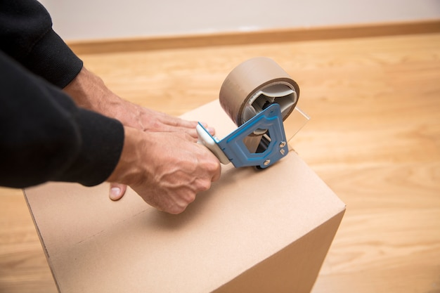 Ręce mężczyzny używającego dozownika taśmy do uszczelnienia opakowania