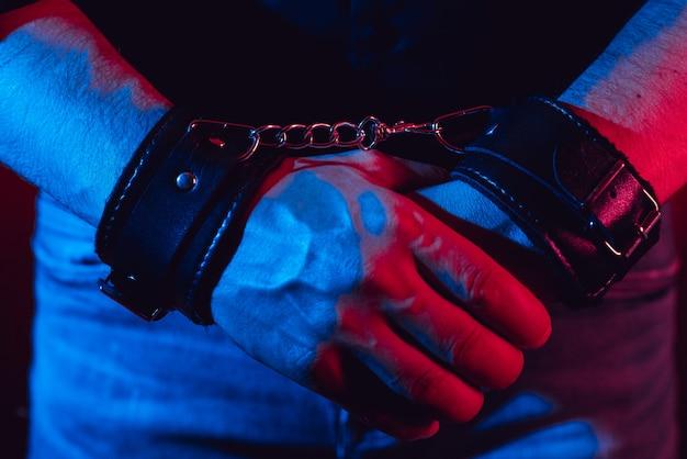 Ręce mężczyzny w czarnych skórzanych kajdankach