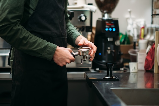 Ręce mężczyzny w czarnym fartuchu, który przygotowuje ekspres do kawy