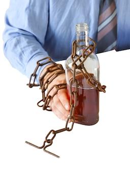 Ręce mężczyzny w stare zardzewiałe łańcuchy w pobliżu butelki. na białym tle. uzależniony od alkoholu. w pułapce pracy biurowej. rutynowa praca. menedżer w pobliżu laptopa.