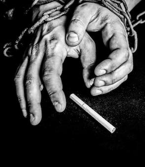 Ręce mężczyzny w stare zardzewiałe łańcuchy w pobliżu papierosa. uzależniony od palenia. niebezpieczny nawyk.