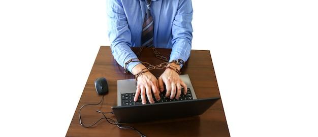 Ręce mężczyzny w starych zardzewiałych łańcuchach. w pułapce pracy biurowej. na białym tle. rutynowa praca. menedżer w pobliżu laptopa.