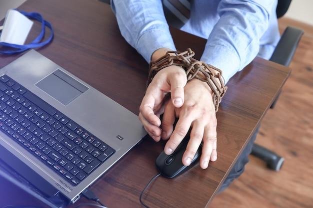Ręce mężczyzny w starych zardzewiałych łańcuchach. w pułapce pracy biurowej. rutynowa praca. menedżer w pobliżu laptopa.
