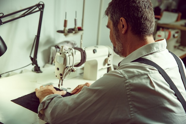 Ręce mężczyzny za szyciem. warsztat skórzany. tkanina vintage przemysłowa. mężczyzna w kobiecym zawodzie. pojęcie równości płci