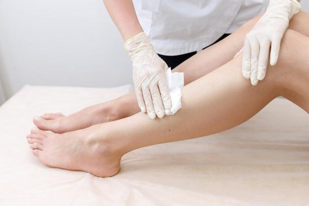 Ręce mistrza będą pocierać stopy depilacją serwetkową