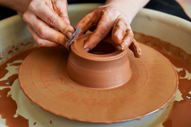 Ręce mistrza garncarza tworzące kształt miski na kole.