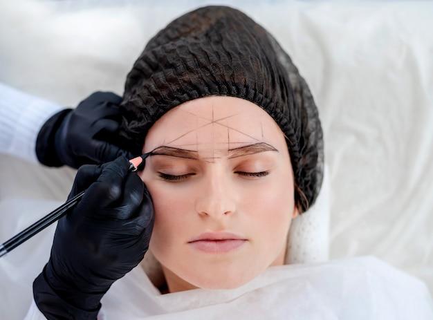 Ręce mistrza makijażu permanentnego rysują nowy kształt brwi dla modelki za pomocą profesjonalnego ołówka. portret zbliżenie