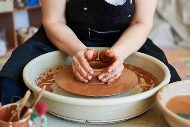 Ręce mistrza pracującego z gliną na kole garncarskim. produkcja rękodzieła.