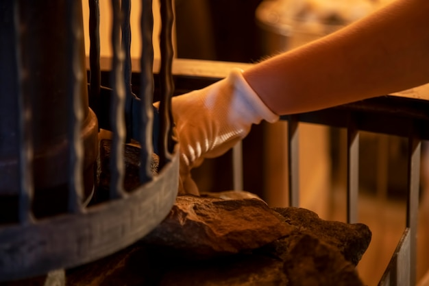Ręce mistrza wkładają kamienie do pieca do sauny. ścieśniać