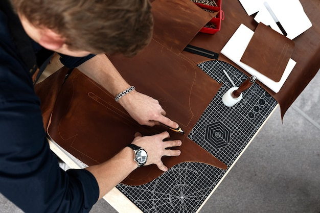 Ręce mistrza wycinają kawałek skóry, zbliżenie kawałka wyrobu skórzanego mistrza do szycia wyrobów skórzanych, rzemieślnika do robienia ręcznie robionych wyrobów skórzanych.