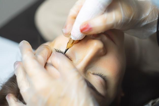 Ręce mistrzyni makijażu permanentnego, która wykonuje tatuaż powieki pochylonej nad nią modelki