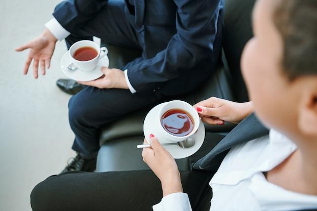 Ręce młoda elegancka bizneswoman mieszanej rasy i jej kolega z filiżanek herbaty omawiających strategie na skórzanej kanapie