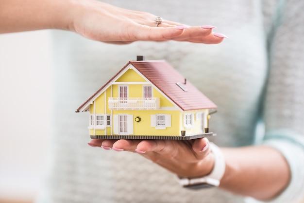 Ręce młoda kobieta trzyma model domu.