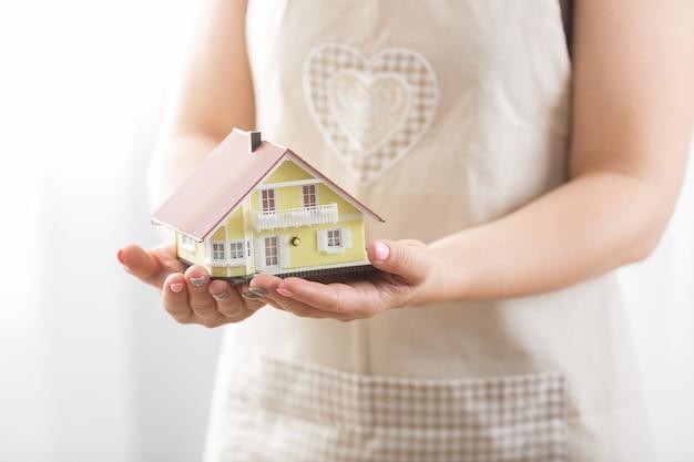 Ręce młoda wężyczka trzyma model domu.