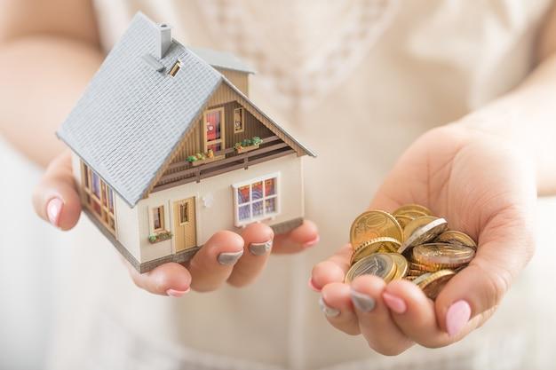 Ręce młoda wężystka trzyma model domu i monety euro.