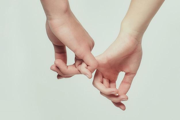 Ręce młodego chłopca i młodej dziewczyny sięgają do siebie. białe tło