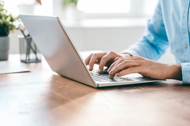 Ręce młodego współczesnego kierownika biura na klawiaturze laptopa podczas pracy nad nowym projektem biznesowym według tabeli