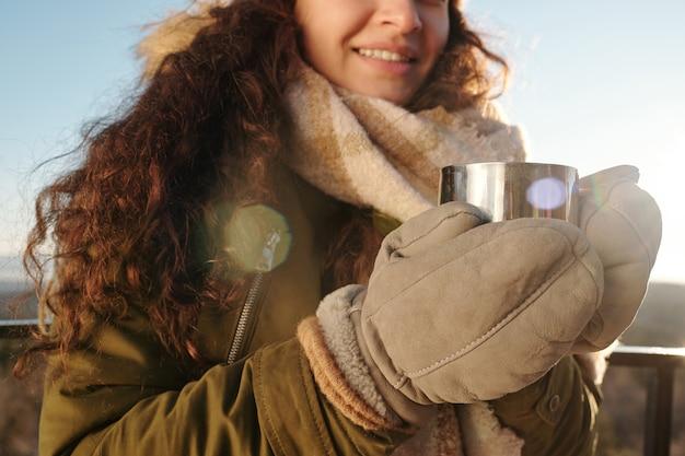 Ręce młodej brunetki w ciepłych rękawiczkach, kurtce i wełnianym szaliku, trzymając metalowy kubek z gorącą herbatą, stojąc w naturalnym środowisku