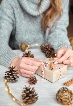 Ręce młodej dziewczyny tworzą i pakują świąteczne i noworoczne prezenty na święta. prezenty dla krewnych i przyjaciół z gratulacjami