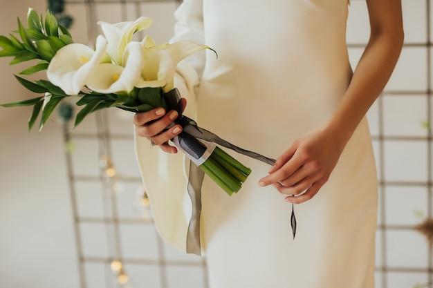 Ręce młodej dziewczyny z pięknym uchwytem do manicure świeżych białych lilii calla