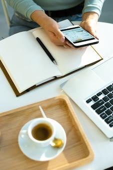 Ręce młodej ekonomistki nad otwartym notatnikiem analizowania danych finansowych w smartfonie przy filiżance herbaty ziołowej w kawiarni