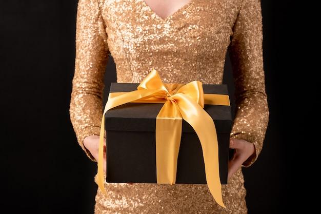 Ręce młodej eleganckiej kobiety w luksusowej sukience trzymając czarne pudełko związane żółtą wstążką z prezentem urodzinowym w środku