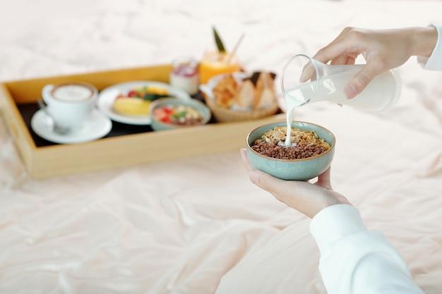Ręce młodej kobiety dodające mleko do miski muesli, gdy siedzi na łóżku z tacą śniadaniową