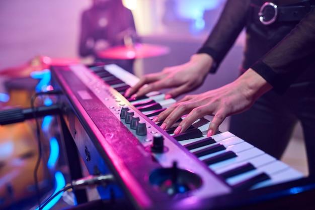 Ręce młodej kobiety dotykające klawiszy syntezatora podczas powtórki