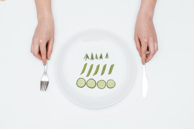 Ręce młodej kobiety jedzącej ogórek, szparagi i rozmaryn na talerzu