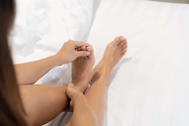 Ręce młodej kobiety masuje jej nogę na łóżku rano. bolesne mięśnie, zwichnięcie lub skurcze.