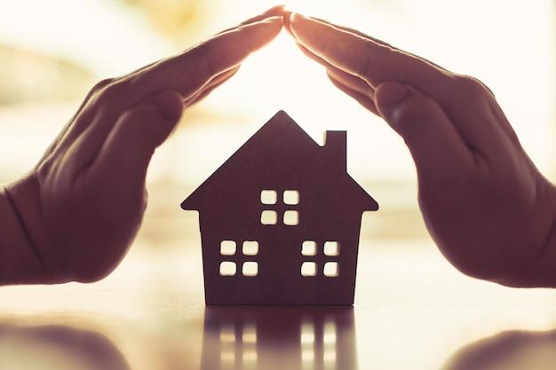 Ręce młodej kobiety otaczają model domu z drewna.