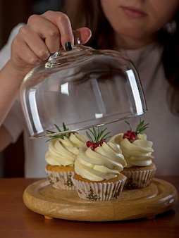 Ręce młodej kobiety trzymając tort urodzinowy selektywnej ostrości.