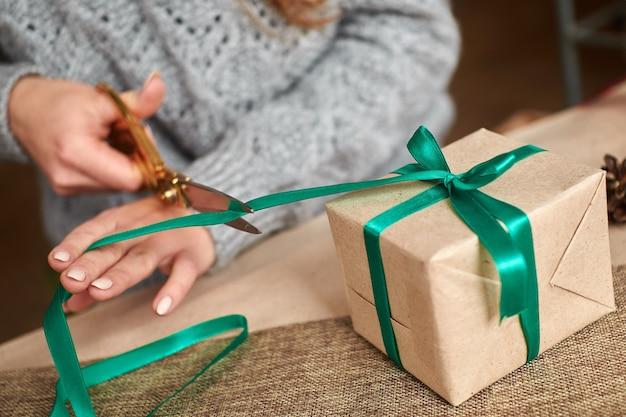 Ręce młodej kobiety tworzą i pakują świąteczne i noworoczne prezenty na święta. prezenty dla krewnych i przyjaciół z gratulacjami. bandaże z zieloną wstążką. poziomy
