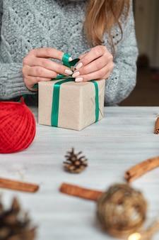 Ręce młodej kobiety tworzą i pakują świąteczne i noworoczne prezenty na święta. prezenty dla krewnych i przyjaciół z gratulacjami. bandaże z zieloną wstążką.