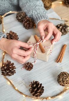 Ręce młodej kobiety tworzą i pakują świąteczne i noworoczne prezenty na święta. prezenty dla krewnych i przyjaciół z gratulacjami. pamiątka rodzinna