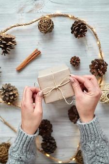 Ręce młodej kobiety tworzą i pakują świąteczne i noworoczne prezenty na święta. prezenty dla krewnych i przyjaciół z gratulacjami. widok z góry