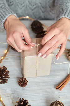 Ręce młodej kobiety tworzą i pakują świąteczne i noworoczne prezenty na święta. prezenty dla krewnych i przyjaciół z gratulacjami