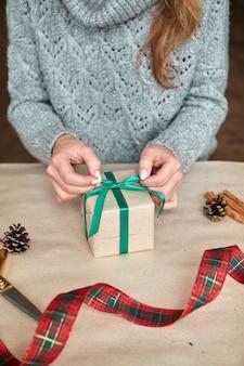 Ręce młodej kobiety tworzą i pakują świąteczne i noworoczne prezenty na święta. prezenty i gratulacje. bandaże z zieloną wstążką. poziomy