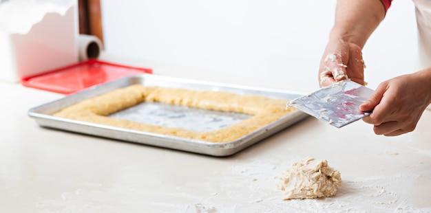 Ręce młodej kobiety za pomocą szpatułki do mieszania ciasta na stole, w tle ciasto na metalowej tacy