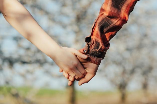 Ręce młodej pary w kwitnący ogród wiosną na zaręczyny. pierścionek na palcu dziewczynki.