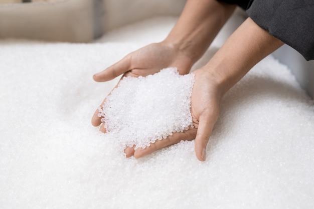 Ręce młodej pracownic dużej współczesnej fabryki przetwórstwa polimerów trzymającej stos nieprzetworzonych białych plastikowych granulek