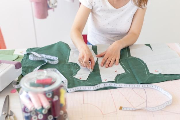 Ręce młodej projektantki robią ślady na nowy produkt do szycia siedząc przy stole