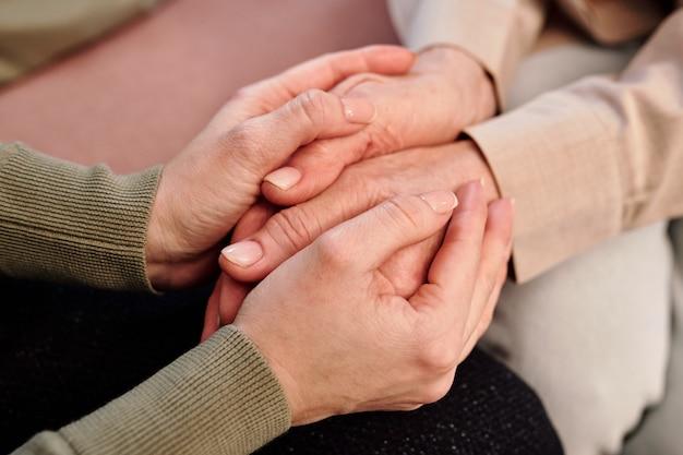 Ręce młodej wspierającej doradczyni trzymającej dłonie dojrzałej kobiety siedzącej obok niej i pocieszające ją w kłopotach