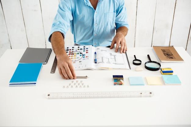 Ręce młody biznesmen siedział przy stole z notatnikiem